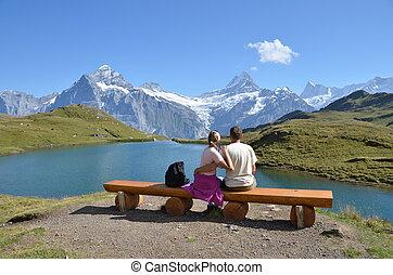 Travelers on a bench enjoying Alpine panorama. Jungfrau...