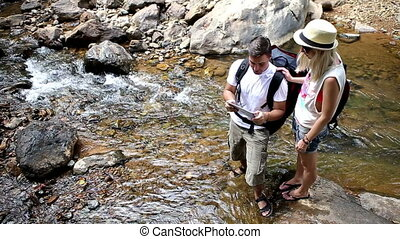 Travelers Planning Route - Tourist couple using travel app...