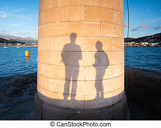 Travelers play with own shadows on  Lighthouse