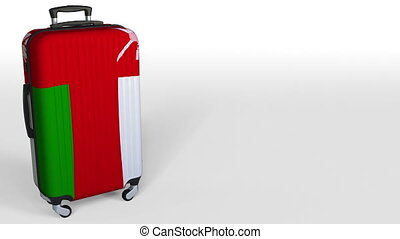 Traveler's suitcase featuring flag of Oman. Omani tourism conceptual animation, blank space for caption