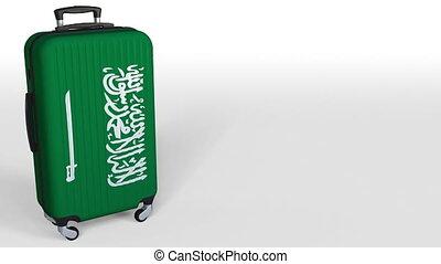 Traveler's suitcase featuring flag of Saudi Arabia. Tourism...