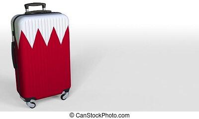 Traveler's suitcase with flag of Bahrain. Bahraini tourism...