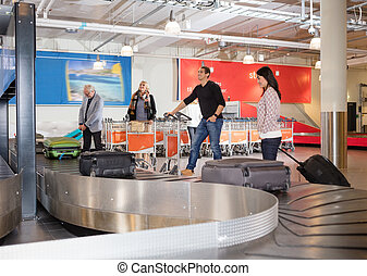 Travelers Waiting For Luggage From Conveyor Belt At Airport