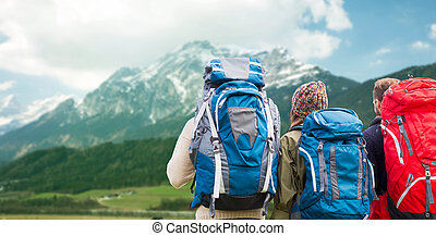 travelers with backpacks hiking in mountains