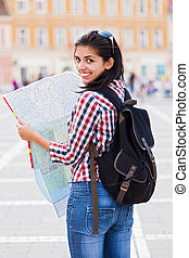 Traveling abroad - Beautiful girl with map smiling in the...
