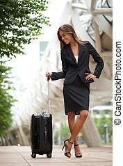 Traveling business woman smiling in the city
