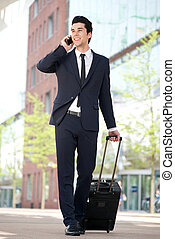 Traveling businessman talking on mobile phone