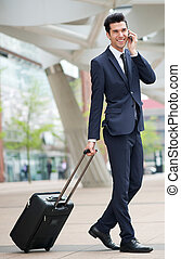 Traveling businessman talking on phone outdoors