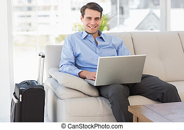 Traveling businessman using laptop sitting on the couch smiling