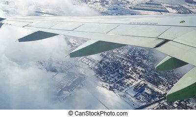 Traveling by air above winter surface. View through an airplane window. Flying over the Moscow through clouds and little turbulence, showing Earth's surface