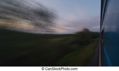 Traveling by passenger train at sunset timelapse. View from the train window.
