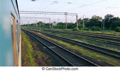 Traveling by train. View of the side of a passenger train while railroad tracks is passing by.