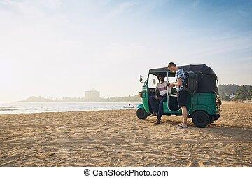 Traveling by tuk tuk taxi - Tuk tuk driver with passenger...
