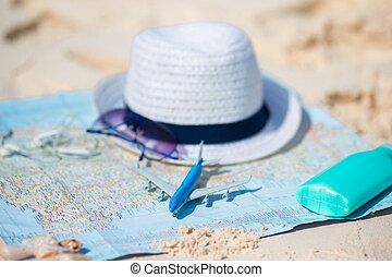 Traveling concept. Hat, suncream, sunglasses on a map of the world.
