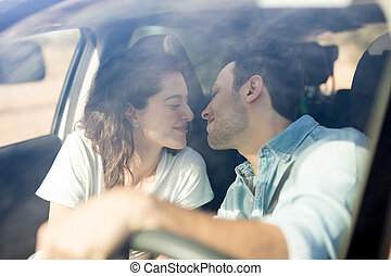 Traveling couple about to kiss in the car