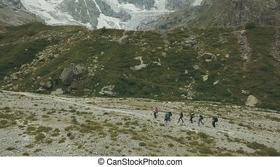 Traveling group walking on mountain trail aerial view....
