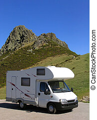 Motorhome parked at the mountain, near a rocky peak