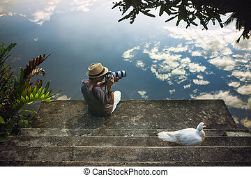 traveling man taking a photograph at old pier against beautiful blue sky reflection on water floor