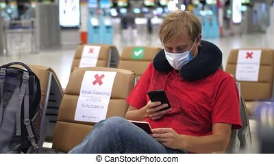 Man wearing medical face mask at the airport uses phone and hold passport to prevent coronavirus infection during world epidemic