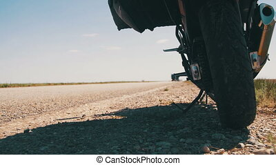 Traveling on a Motorcycle. Moto Travel. Motorcycle Stands near the Road and Passing Cars