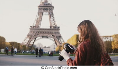 Traveling teenager taking photos of the Eiffel tower in...