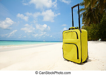 Suitcase on the beach with white sand, sunny sky and palms representing vacation travel concepts