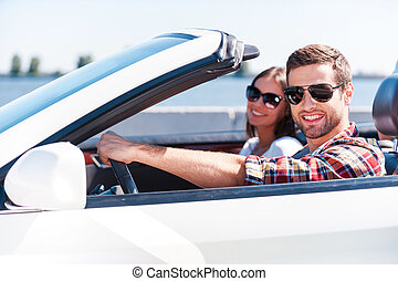 Traveling with comfort. Happy young couple enjoying road trip in their white convertible while both looking at camera and smiling
