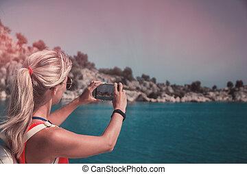Traveling woman take a photo mountain view, travel concept