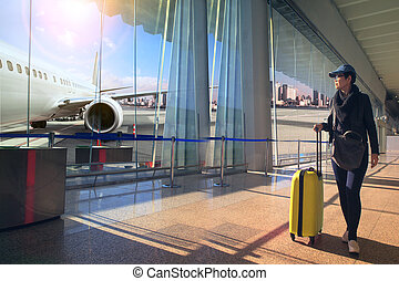 traveling woman with luggage in airport terminal