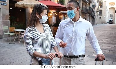 Traveling young spouses wearing medical masks to prevent viral infection strolling with luggage along city street on spring day