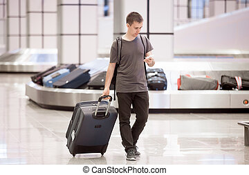 Traveller at conveyor belt texting - Young handsome...