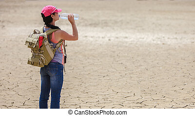 Traveller drinking water from bottle in the desert