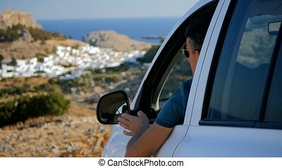 Traveller enjoys the panoramic view from his car