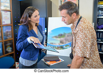 traveller getting holiday brochure in travel agency