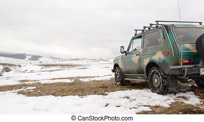 Traveller near off-road vehicle on snowy mountain plateau
