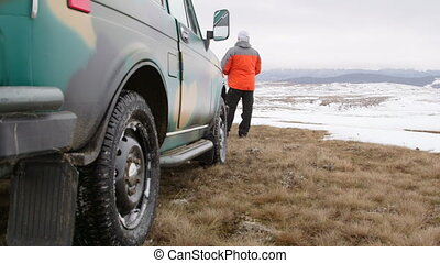 Traveller near off-road vehicle on snowy highland - Man...