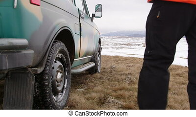 Traveller standing near the SUV on snowy mountain plateau -...