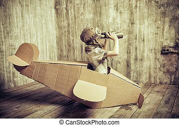 traveller - Cute dreamer boy playing with a cardboard...