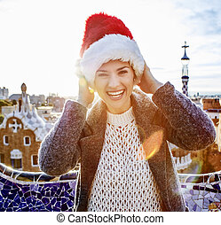 traveller woman in Santa hat at Guell Park having fun time -...