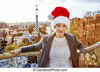 traveller woman in Santa hat at Guell Park sitting on bench...