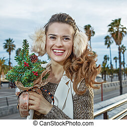 traveller woman with a little Christmas tree looking into the distance