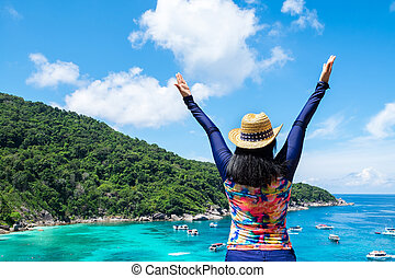 Traveller woman with colorful swimming suit raised arms to sky at top of mountain with blue ocean view and speed boat in sea, Summer vacation traveling