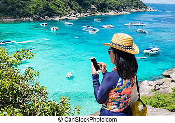 Traveller woman with colorful swimming suit use mobile take photo of view at top of mountain and speed boat in sea, Summer vacation traveling