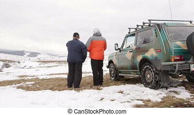 Travellers near off-road vehicle on snowy highland