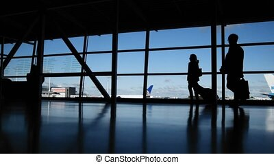 Travellers with suitcases and baggage in airport walking to...