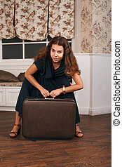Travelling concept with woman sitting on suitcase