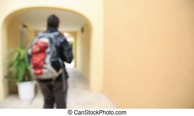 Travelling - Out of focus departure of man with backpack
