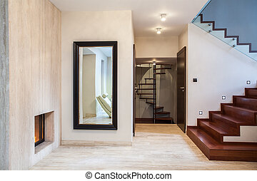 Travertine house: huge mirror and wooden stairs