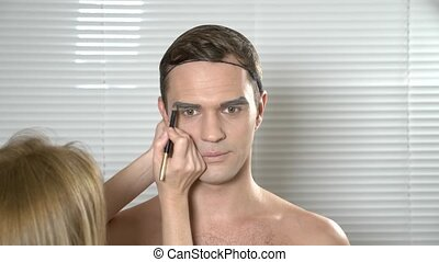 Travesty make up. a young man makes himself a transsexual mencup. 4k, slow motion. make-up artist does makeup guy