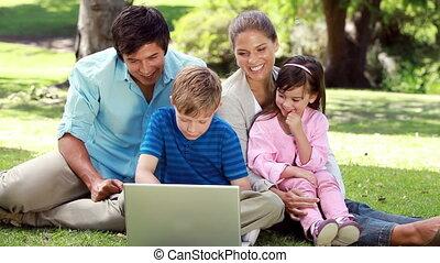 trawa, laptop, uśmiechanie się, rodzina, posiedzenie